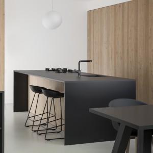 Wyspa kuchenna pełni jednocześnie funkcję praktycznego baru. Hokery ze szczupłymi nogami i delikatnymi siedzeniami wpisują się w minimalistyczną stylistykę wnętrza. Projekt: i29 interior architects. Fot. Ewout Huibers.