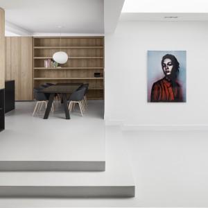 Jadalnię i kuchnię zlokalizowano na delikatnym podwyższeniu, skomunikowanym z salonem dwoma niewielkimi schodkami. W jadalni stoi efektowny, kompletnie czarny stół oraz krzesła z czarnymi siedzeniami. Nad stołem zawisła nowoczesna, designerska, biała lampa. Projekt: i29 interior architects. Fot. Ewout Huibers.