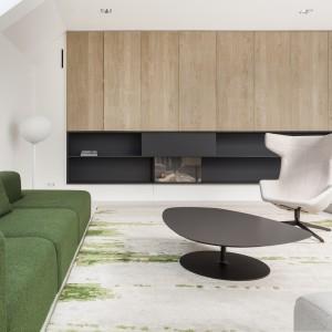 Meble wypoczynkowe w salonie kolorystycznie komponują się z ręcznie utkanym dywanem. Stolik kawowy kolorem i teksturą koresponduje z zabudową ścienną wokół kominka i w kuchni. Projekt: i29 interior architects. Fot. Ewout Huibers.
