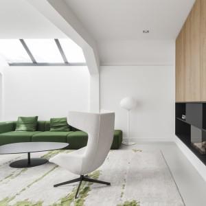 Biała lampa stojąca w rogu salonu niemal całkowicie wtapia się w, stanowiącą dla niej tło, białą ścianę. Odważny i niebanalny efekt dekoracyjny powtórzono, ozdabiając półkę nad kominkiem, czarną figurką ptaka, który również niemal znika na tle czarnej zabudowy. Projekt: i29 interior architects. Fot. Ewout Huibers.