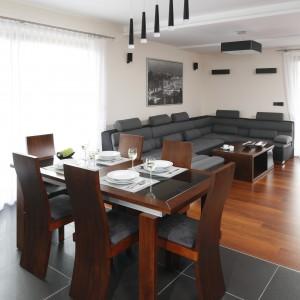 Otwartą przestrzeń dzienną jadalnia dzieli z salonem. Aranżację zdominowała – zgodnie z życzeniem inwestorów – gama ciemnych kolorów. Fot. Bartosz Jarosz.