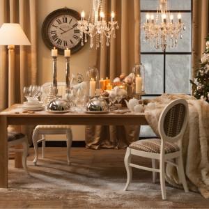 Biel i srebro to główne elementy dekoracji stołu. Klasyczne świeczniki, figurka renifera oraz piękne kieliszki tworzą niezwykle elegancki wystrój. Fot. Almi Decor.