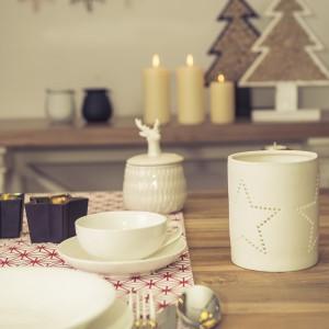 Biała zastawa stołowa i  srebrne sztućce to prosta, ale elegancka propozycja. Świece, świeczniki, ozdobne choinki z drewna oraz ceramiczny pojemnik z jeleniem doskonale uzupełniają aranżację. Fot. Duka Polska.