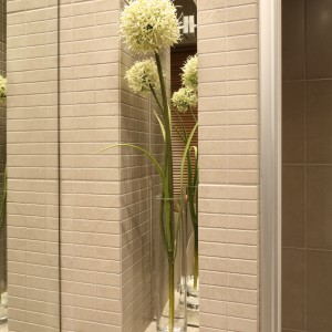 Półki w łazience przy wykończono delikatną, ozdobną mozaiką. Wnęka przy lustrze pozwala wyeksponować elementy dekoracyjne. Fot. Bartosz Jarosz.