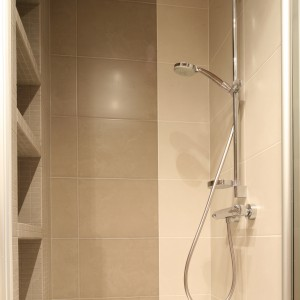 We wnęce prysznicowej zainstalowano zestaw natryskowy (bateria prysznicowe, drążek i słuchawka). Na przeciwko półki wnękowe na kosmetyki, wykończone mozaiką.  Fot. Bartosz Jarosz.