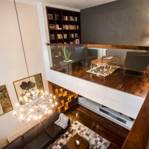 Widok na bibliotekę oraz salon. Antresolę okala balustrada wykonana z bezpiecznego, hartowanego szkła. Szklane powierzchnie dodają wnętrzu lekkości i pięknie komponują się z wieńczącym je drewnem. Otwartą przestrzeń doświetla, wpadające przez okna naturalne światło. Projekt: Pracownia Projektowania Wnętrz Viva Design, Fot. Tadeusz Poźniak.