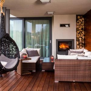 Do wypoczynku na świeżym powietrzu zachęcają eleganckie meble tarasowe, efektowne siedzisko-huśtawka oraz kominek z paleniskiem od strony tarasy. Ociepli on najzimniejsze wieczory i zbuduje nastrój. Elewacje i posadzkę wykonano z drewna, które wizualnie buduje przytulny klimat. Projekt: Pracownia Projektowania Wnętrz Viva Design, Fot. Tadeusz Poźniak.