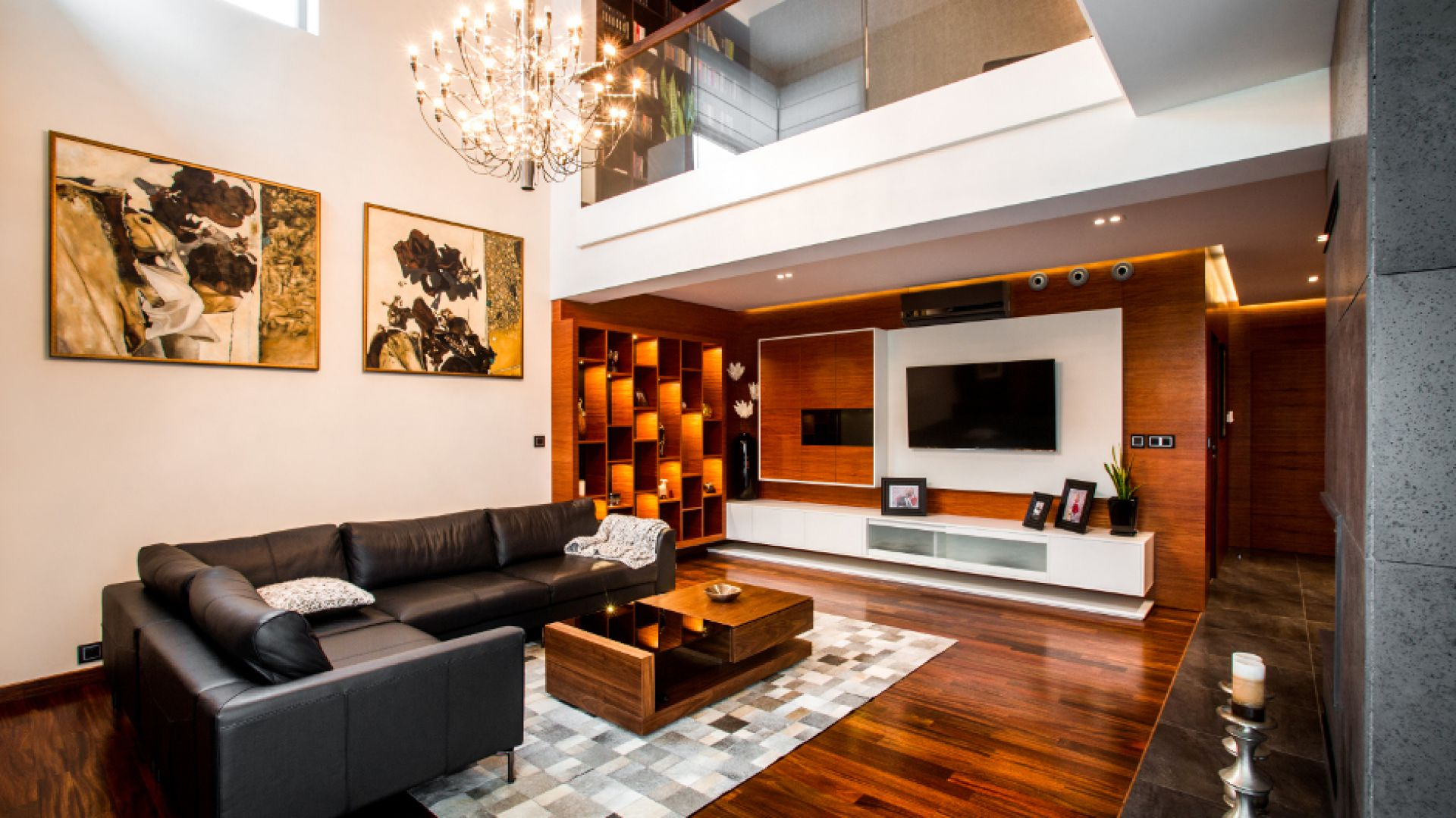Ścianę wokół telewizora wyłożono naturalnym drewnem. Na powierzchni zamontowano białą płytę, w której centralnym punkcie zawisł telewizor. Jest on pięknie eksponowany przez, kontrastującą z czernią i okalającym panel drewnem, biel. Projekt: Pracownia Projektowania Wnętrz Viva Design, Fot. Tadeusz Poźniak.