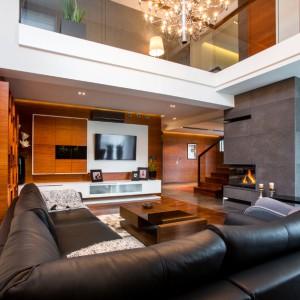 W przestronnym salonie spotykają się różnorodne, szlachetne materiały. Podłogę wykończono litym drewnem denya, ścianę wokół kominka pokrywa modny beton architektoniczny, z kolei dywan w strefie wypoczynkowej jest wykonany ze skóry. Projekt: Pracownia Projektowania Wnętrz Viva Design, Fot. Tadeusz Poźniak.