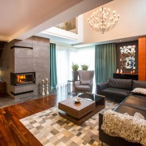 Elegancki salon z kominkiem zachęca do wypoczynku. Duży, przytulny narożnik, tekstylia w oknach oraz drewno w ciepłym, bursztynowym kolorze, nadają wnętrzu domowy charakter. Projekt: Pracownia Projektowania Wnętrz Viva Design, Fot. Tadeusz Poźniak.