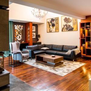 W salonie dekorację tworzą efektowne meble i narożny, estetyczny kominek. Ciekawy efekt zapewnia oryginalny regał z asymetrycznymi półkami, zamontowanymi na czarnym, kontrastującym z ciepłym brązem, tle. Wzrok przyciąga piękny włoski żyrandol, obrazy na wysokiej ścianie oraz kolarz na ścianie za fotelem. Całość nadaje pokojowi dziennemu unikalny klimat. Projekt: Pracownia Projektowania Wnętrz Viva Design, Fot. Tadeusz Poźniak.