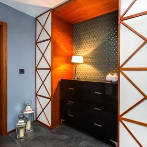 Podłogę w przedpokoju wykończono eleganckimi płytkami w kolorze ciemnej szarości. Na tle jaśniejszej, szarej ściany wyeksponowano oryginalną zabudowę wokół czarnej, połyskującej komody. Ścianę bezpośrednio stykającą się z komoda pokryto efektowną tapetą - również w odcieniu szarości. Projekt: Pracownia Projektowania Wnętrz Viva Design, Fot. Tadeusz Poźniak.