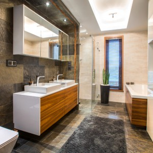 W domu znajdują się trzy łazienki. Główna łazienka domowników zlokalizowana jest na piętrze. Na podłodze i ścianach położono kamień naturalny oraz płytki. Fronty mebli o białych korpusach, pokryto drewnianym dekorem, nadającym łazience, wygląd salonu kąpielowego. Projekt: Pracownia Projektowania Wnętrz Viva Design, Fot. Tadeusz Poźniak.