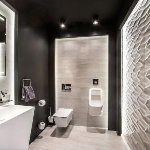 Na parterze zaplanowano toaletę dla gości. Wyróżnia się ona kolorystycznie na tle innych pomieszczeń. Urządzona w efektownej kompozycji szarości, bieli i czerni przyjmuje ona niezwykle elegancki charakter. Projekt: Pracownia Projektowania Wnętrz Viva Design, Fot. Tadeusz Poźniak.