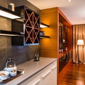 Jadalnię i kuchnię spaja ściana, na której zlokalizowano szafkę z miejscem na przechowywanie wina oraz elegancki regał. Inną funkcję pomieszczeń zaznaczono poprzez zastosowanie różnych kolorów - w jadalni królują brązy, kuchnia jest biało-szara. Projekt: Pracownia Projektowania Wnętrz Viva Design, Fot. Tadeusz Poźniak.
