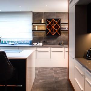 Kuchnia z wyspą urządzona została w nowoczesnym stylu i modnych kolorach. Białe fronty mebli są gładkie, z prostymi uchwytami, wykończone na połysk. Blat kuchenny wykonany z kwarcytu pięknie komponuje się z szarymi płytkami na podłodze i ścianach. Projekt: Pracownia Projektowania Wnętrz Viva Design, Fot. Tadeusz Poźniak.