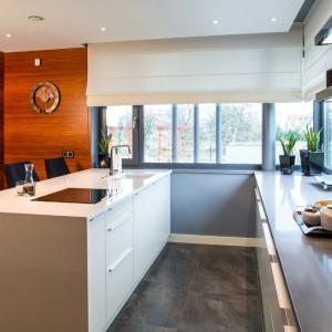 W centrum kuchni ustawiono sporych rozmiarów wyspę kuchenną, na której usytuowano zlewozmywak i płytę kuchenną. Szeroki blat wyspy może służyć również za powierzchnię, przeznaczoną do serwowania drinków, a sama wyspa zamienić się w domowy bar. Na tę okoliczność, zaplanowano tapicerowane hokery. Projekt: Pracownia Projektowania Wnętrz Viva Design, Fot. Tadeusz Poźniak.