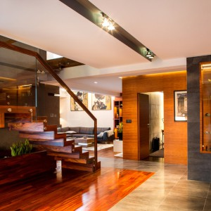 Na hol wychodzą otwarte schody dywanowe. Podobnie jak wiele elementów we wnętrzu, zostały one wykonane z drewna. Szklana balustrada nadaje im lekkości, a drewniane poręcze elegancji. Z drewna wykonano także doniczkę, którą wpasowano w wolną przestrzeń pod schodami. Na ścianach okładziny fornirowane z drewna naturalnego. Bezprzylgowe drzwi pasują wizualnie do lekkiej aranżacji. Projekt: Pracownia Projektowania Wnętrz Viva Design, Fot. Tadeusz Poźniak.