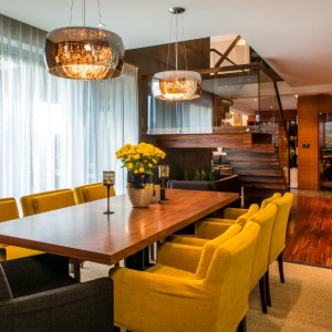 W sąsiedztwie otwartej klatki schodowej, urządzono jadalnię. Drewnianemu, prostemu stołowi towarzyszą tapicerowane krzesła w pięknym, jesiennym kolorze żółci oraz dwa szare - po przeciwległych stronach stołu. Na podłodze dywan oraz drewno lite denya, olejowane. Projekt: Pracownia Projektowania Wnętrz Viva Design, Fot. Tadeusz Poźniak.