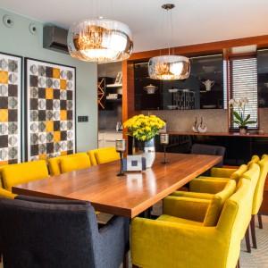 Nad stołem zawisły efektowne, połyskujące lampy. Razem z przeszklonym regałem, stanowią one element dekoracyjny wnętrza. Uwagę przykuwają również geometryczne motywy na ścianach, harmonizujące z kolorystyką pomieszczenia. Projekt: Pracownia Projektowania Wnętrz Viva Design, Fot. Tadeusz Poźniak.