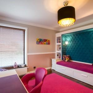 W pokoju dziewczynki obowiązkowo znalazł się róż! Różowy jest miękki dywan, krzesło przy biurku oraz tapicerka łóżka. To z kolei stanowi efektowny mebel, połączony z zabudową z praktycznymi półkami oraz z pikowanym zagłówkiem w żywym, turkusowym kolorze. Projekt: Pracownia Projektowania Wnętrz Viva Design, Fot. Tadeusz Poźniak.
