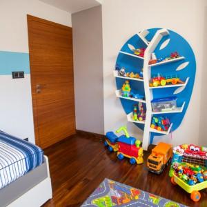 W pokoju synka na jednej ze ścian ustawiono fantazyjny mebel, z półkami imitującymi gałęzie drzew i gotowymi niebieskimi plecami w roli korony liści. Projekt: Pracownia Projektowania Wnętrz Viva Design, Fot. Tadeusz Poźniak.
