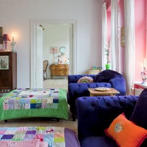 Granatowe kanapy są kolejnym wyrazistym elementem tego wnętrza – właścicielka nie bała się zestawić z nimi kolorowych narzut i ścian w odważnych barwach. Fot. Polly Eltes/Narratives.