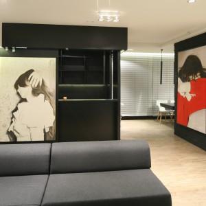 Jadalnia i kuchnia chowają się za czarną ścianką działową, pozostając jedynie delikatnie widoczne z poziomy salonu. Główną ozdobę salonu stanowi obraz autorstwa Anny Pietrzak. Fot. Bartosz Jarosz.