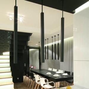 Na blatem kuchennym zawisły efektowne czarne lampy, komponujące się kolorystycznie z czarnym sufitem. Fot. Bartosz Jarosz.