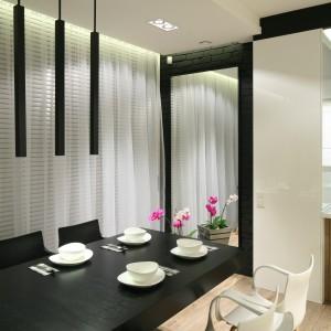 Na ścianie w jadalni zamontowano duże lustro, które odbija widok na stół jadalniany, przedłużając perspektywę widokową i powiększając optycznie wnętrze. Fot. Bartosz Jarosz.