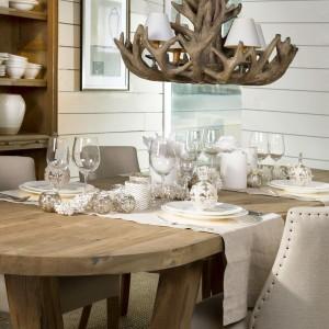 Drewniany stół pięknie wygląda udekorowany białymi obrusami i zastawą. Białą, klasyczną porcelanę i proste, eleganckie szkło uzupełniają urokliwe latarenki oraz ozdobne białe bombki. Fot. Flamant.