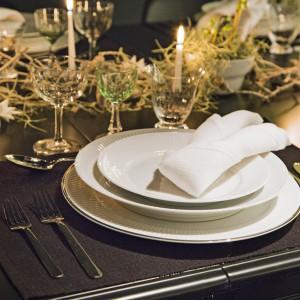 Niekiedy mniej znaczy więcej - tak jak tutaj. Eleganckie połączenie prostej białej zastawy stołowej, srebrnych sztućców i delikatnych kryształów. Stół delikatnie udekorowano gałązkami położonymi wzdłuż centrum stołu, subtelnymi, szczupłymi świeczkami oraz niewielkimi białymi gwiazdkami. Fot. Royal Copenhagen.