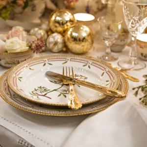 Piękna, elegancka dekoracja stołu. Biały, koronkowy obrus pięknie eksponuje talerze z pozłacanym dekorem. Całości dopełniają posrebrzane i złote bombki oraz kryształowe kieliszki. Fot. Royal Copenhagen.
