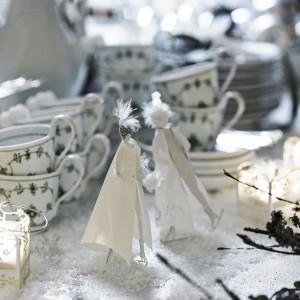 """Urokliwa, biała aranżacja w zimowym klimacie. Białą porcelaną ozdabiają delikatne wzory z motywem świątecznych gałązek choinkowych. Na stole """"tańcują"""" białe aniołki. Fot. Marks and Spencer."""