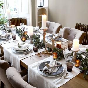 Biel i szarości urozmaicono latarenkami - pozłacanymi i z brązowego szkła. Ocieplają one świąteczny stół naturalnym ogniem oraz swoją barwą. Zamiast tradycyjnego obrusu - białe bieżniki. Fot. Occa-Home.