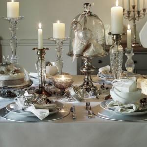 Pięknie udekorowany świąteczny stół. Biały obrus zastawiono pięknymi świecznikami oraz paterami ze szklanymi pokrywami. Pod kloszem schowano posrebrzaną bombkę, spoczywającą na tkaninie - akcent stanowi główny element dekoracji stołu. Fot. Marks and Spencer.