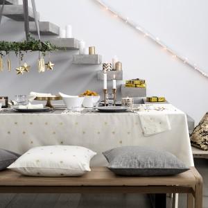 Nowoczesna, oszczędna dekoracja stołu świątecznego. Biały, prosty obrus z dekorem w złote gwiazdki nawiązuje do zawieszonych nad stołem pozłacanych bombek. Ze złotymi gwiazdkami komponują się miedziany świecznik i patera. Fot. H&M Home.