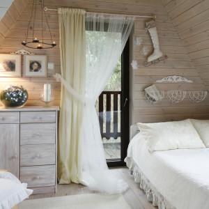 Sypialnia jest oazą spokoju. Otoczona z trzech stron oknami, przez które zagląda las, umieszczona na poddaszu i utrzymana w bielach i ecru, emanuje nastrojowym klimatem. Posiada swój własny balkon, z którego roztacza się widok na ogród i las. Fot. Bartosz Jarosz.