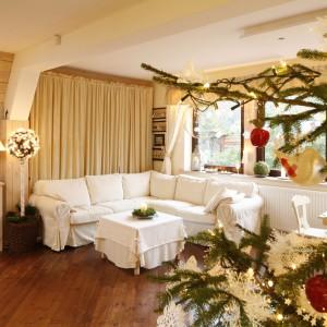 Rodzina lubi odpoczywać na jasnej sofie narożnej. Zimą można stąd śledzić ogień w kominku, latem tuż za nią funkcjonuje wyjście na taras. Fot. Bartosz Jarosz.