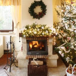 Świąteczne dekoracje w tym domu to nie tylko choinka. To również wianuszki oraz całe naręcza świerkowych gałązek, przeplatanych choinkowymi lampkami, wstążkami, szyszkami czy uszytymi z lnu drobiazgami. Fot. Bartosz Jarosz.