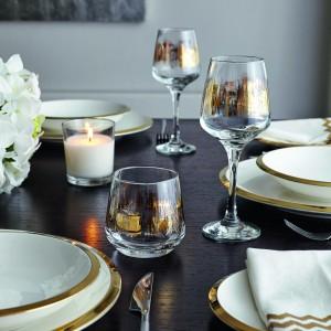 Propozycja dla miłośników eleganckiego minimalizmu. Dekorację stanowią delikatne zdobienia na zastawie stołowej: złote obramowania talerzy i wzory na kieliszkach i szklankach. Świąteczny klimat buduje paląca się biała świeczka. Fot. F&F Home.