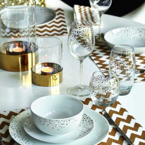 Prostota ozdobiona złotymi akcentami. Tutaj w formie geometrycznego motywu na serwetkach, podstawek pod świeczki i kropkowanych wzorów na zastawie stołowej. Fot. F&F Home.