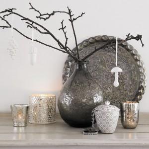 Czasem wystarczy kilka gałązek ozdobionych zawieszkami, żeby wprowadzić do wnętrza bożonarodzeniową atmosferę. Srebrny wazon i stylowe błyszczące lampiony znakomicie uzupełniają aranżację. Fot. Green Gate.