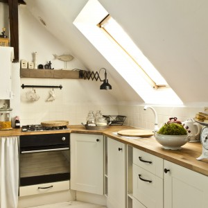 Pojemne szafki i retro etażerka z powodzeniem pomieściły potrzebne gospodyni kuchenne wyposażenie. Ciekawą w formie lampkę, niegdyś używaną w fabryce, własnoręcznie odnowił Piotr.