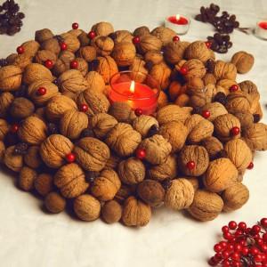 Oryginalny wianek z orzechów włoskich, ożywiony czerwonymi dodatkami, to urokliwa ozdoba bożonarodzeniowego stołu. Fot. Bosch.