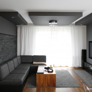 W eleganckim salonie zdecydowano się na modne szarości. Zdobią one ścianę z telewizorem oraz sufit. Projekt: Michał Mikołajczak. Fot. Bartosz Jarosz.