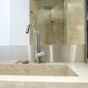 Łazienka został wykończona marmurem, z którego wykonano umywalkę - według indywidualnego projektu, w kształcie  przypominającym koryto oraz blaty po obu stronach misy. Projekt: Izabela Mildner. Fot. Bartosz Jarosz.