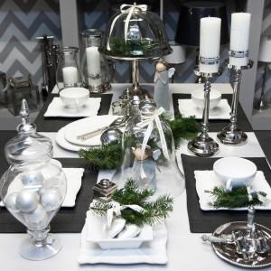 Elegancki sposób na udekorowanie świątecznego stołu: stonowane szarości, biel i srebro oraz odrobina gałązek choinkowych. Wśród tej spokojnej aranżacji, żywym, wesołym elementem są urocze figurki aniołków - jeden stojący na stole, drugi schowany pod kloszem. Fot. Decoratore.