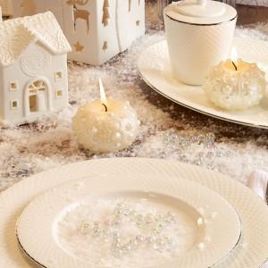 Stół w bieli, a na nim delikatne dekoracje w postaci białego domku oraz paczki z prezentem, w których wycięto niewielkie otwory. Przyjęły one kształt między innymi, reniferów. Fot. Villa Italia.