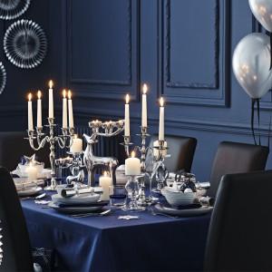 Srebrne świeczniki stanowią punkt centralny aranżacji tego świątecznego stołu. Wśród nich uwagę przyciąga jednak szczególnie jeden - w kształcie renifera, którego rogi posłużyły za podstawki do niewielkich świeczek. Fot. Sainsbury's.